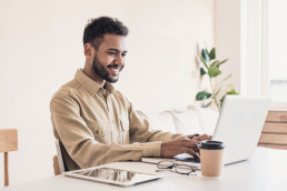 Person smiling at laptop using Loxo ATS software for remote recruitment